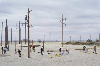 Workers putting up telephone poles, Nebraska, 2012