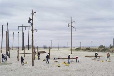 Workers putting up telephone poles, Nebraska, 2012
