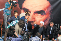 Iranian President Hassan Rouhani at a rally during his presidential campaign in front of a poster of Ayatollah Khomeini, Tehran, June 1, 2013