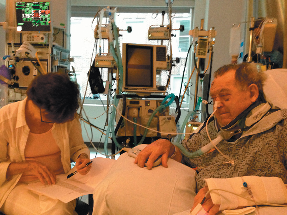 """Arnold Relman in the surgical intensive care unit at Massachusetts General Hospital, the week after his accident. His wife, Marcia Angell, is helping him correct galleys of his August 15, 2013, article in these pages, """"Obamacare: How It Should Be Fixed."""""""