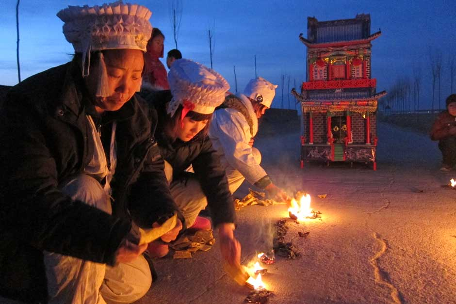 A family in traditional mourning attire burn paper money in front of a paper mansion. The return of collective religious traditions is part of Chinese people's search for meaning and stability.