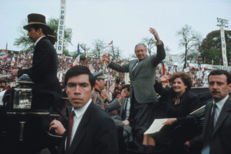 Augusto Pinochet and his wife, Lucía, being paraded around a stadium in a carriage, Talca, Chile, 1988