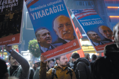 Protesters with placards of Turkish Prime Minister Recep Tayyip Erdoğan and the US-based Turkish cleric Fethullah Gülen during a demonstration against corruption, Istanbul, December 25, 2013. The text on the placards says 'We will cast them down!'