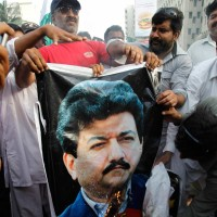 Supporters of Pakistan's military, burning a poster of news anchor Hamid Mir, Karachi, Pakistan, April 26, 2014