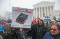 Protesters outside the Supreme Court as it heard arguments in two cases, brought by three Christian-owned ­companies, challenging the Affordable Care Act's requirement that businesses provide female employees with insurance that covers contraception, Washington, D.C., March 25, 2014