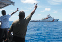 Filipino crew members gesturing at a Chinese Coast Guard vessel that tried to block their supply ship from approaching the decrepit BRP Sierra Madre, where Filipino Marines are stationed to guard the disputed Ayungin reef, Spratly Islands, South China Sea, March 2014