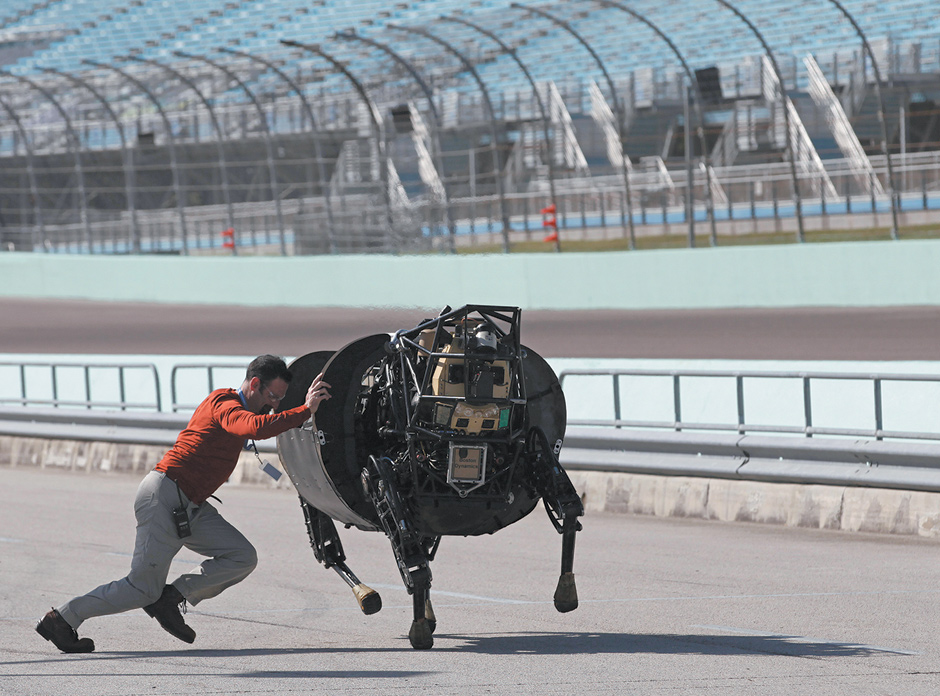 The LS3, a four-legged rough-terrain robot designed by Boston Dynamics with funding from DARPA and the US Marine Corps to accompany soldiers anywhere they go on foot, and to help respond to natural and man-made disasters, at the DARPA Robotics Challenge Trials, Homestead-Miami Speedway, Florida, December 2013. That month, Boston Dynamics was acquired by Google, which says it will honor existing contracts with DARPA but is rejecting other DARPA funding.