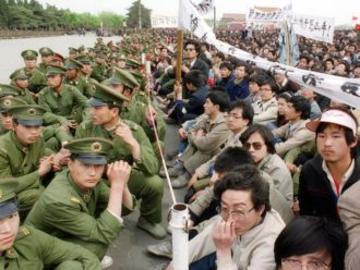 Pro-democracy student protesters sit face to face with policemen outside the Great Hall of the People in Tiananmen Square, Beijing, April 22, 1989