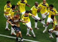Colombia's James Rodriguez (10) and Pablo Armero, to his left, dancing with teammates after a goal against Ivory Coast, June 19, 2014