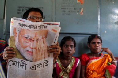 A man reading a Bengali newspaper with a story about Narendra Modi, Calcutta, India, May 17, 2014