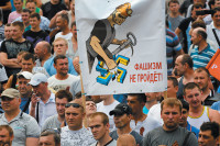 Local miners at a rally in support of the Donetsk People's Republic with a banner showing a miner smashing a swastika in the color of Ukraine's flag, May 28, 2014