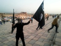 A fighter with an ISIS flag and weapon in Mosul, Iraq, June 23, 2014