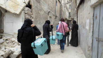 Health workers carrying polio vaccine, as part of a vaccination campaign organized by the opposition Assistance Coordination Unit, Aleppo, Syria, May 5, 2014
