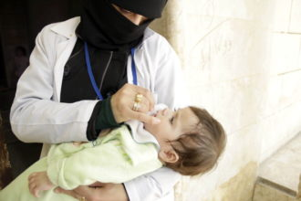 A health worker giving polio vaccine drops to a child, as part of a vaccination campaign organized by the opposition Assistance Coordination Unit, Aleppo, Syria, May 5, 2014