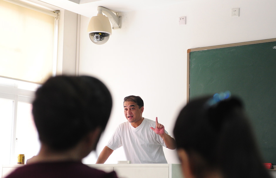 Ilham Tohti lecturing in Beijing with a surveillance camera above him, June 12, 2010