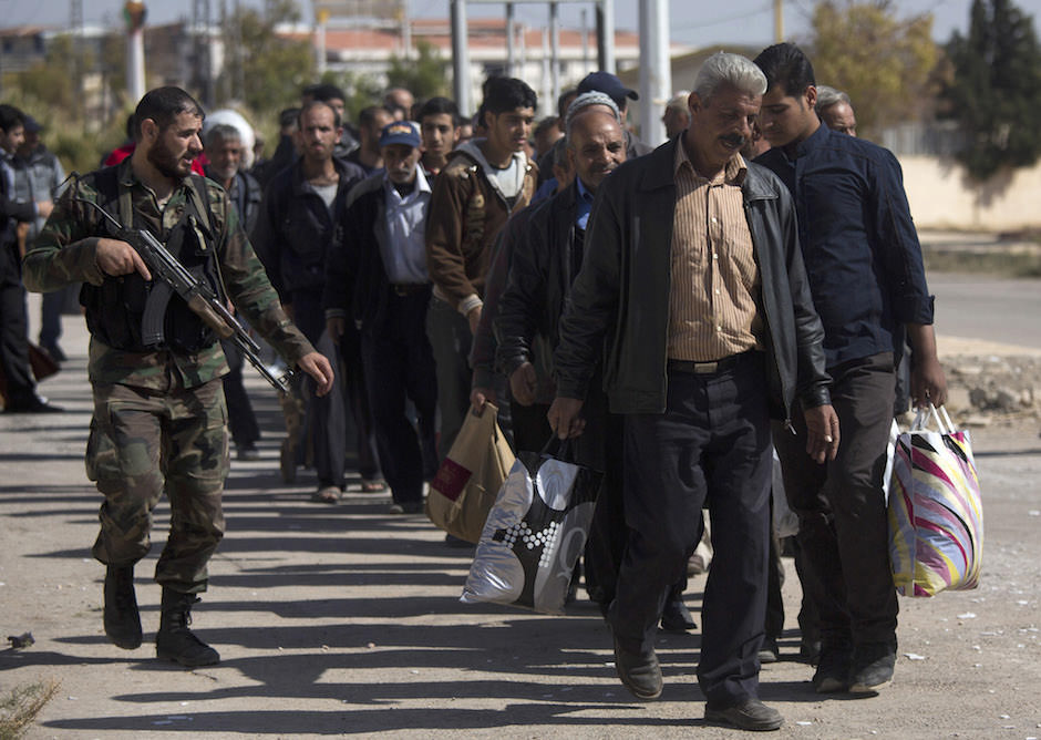 A Syrian soldier escorting men from Moadamiyeh, a rebel-held suburb of Damascus, following a truce deal to relieve blockades and allow humanitarian aid to reach the area, October 29, 2013