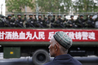 A Uighur man watching a convoy of Chinese paramilitaries in Urumqi, Xinjiang Uighur Autonomous Region, May 23, 2014