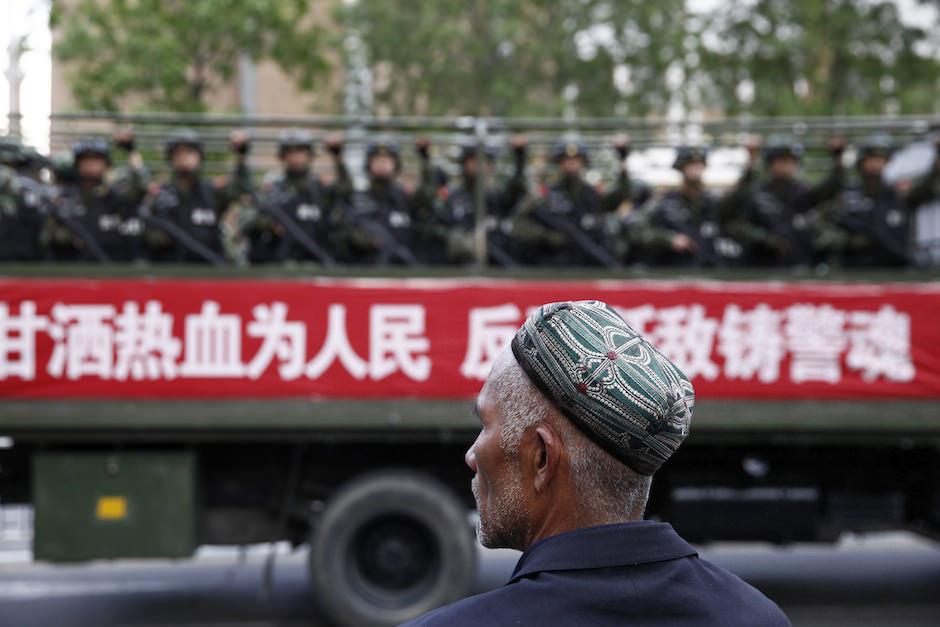 A Uighur man watching a convoy of Chinese paramilitaries in Urumqi, Xinjiang Uighur Autonomous Region, May 23, 2014