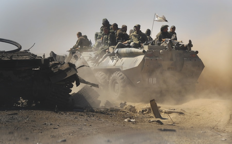 Rebels driving past destroyed Ukrainian military vehicles near Novokaterinivka, Ukraine, September 2, 2014