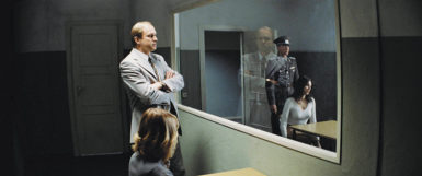 A Stasi official observing the interrogation of the lover of an East German playwright whose loyalty to the state is questioned, in Florian Henckel von Donnersmarck's film The Lives of Others, 2006