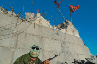 A rebel soldier guarding the ruins of the Savur-Mogila Memorial, September 6, 2014. The memorial, which commemorated the Soviet capture of a strategic hill near Snizhne in eastern Ukraine, was destroyed in fighting between Ukrainian and rebel forces in August 2014. According to Tim Judah, 'journalists are told not to take pictures that show the faces of rebel fighters.' For more of his photographs from eastern Ukraine, see the NYRgallery blog, nybooks.com/ukraine-war.