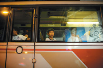 A boy watching pro-democracy demonstrators from a school bus near a protest site in Hong Kong, October 2014