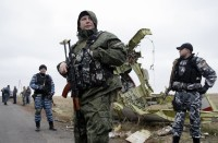Pro-Russian rebels stand guard at the crash site of Malaysian Airlines jet MH-17 near Donetsk, Ukraine, November 11, 2014