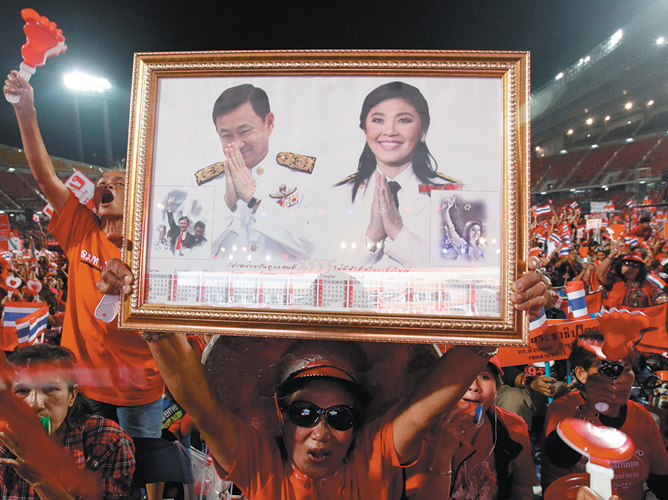 A Red Shirt supporter holding pictures of Thailand's ousted prime minister Yingluck Shinawatra and her brother, former prime minister Thaksin Shinawatra, at a rally in Bangkok, November 2013