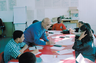 Bob Moses, civil rights activist and founder of the Algebra Project, a program that 'uses mathematics as an organizing tool to ensure quality public school education for every child in America,' with students at Lanier High School, Jackson, Mississippi, 2002
