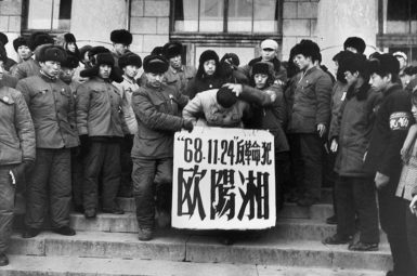Ouyang Xiang, son of a denounced former Party secretary in Heilongjiang province, being persecuted during the Cultural Revolution for sending an unsigned letter to the local revolutionary committee in his father's defense, Harbin, November 1968. The sign around his neck bears his name and the date of his offending letter. When he tried to shout 'Long live Chairman Mao,' his mouth was stuffed with a glove. Several days later he was pushed out of a third-story window; the official report called his death a suicide.