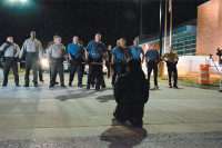 Reverend Osagyefo Sekou, a leader of the protest movement, kneeling in prayer between police and a crowd of protesters outside the police station, Ferguson, Missouri, September 2014