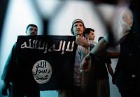 A suspected al-Qaeda militant (center) holding an Islamist banner,