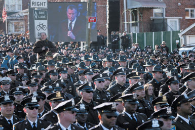 Law enforcement officers turning their backs on a live screen of Mayor Bill de Blasio as he delivered a eulogy for NYPD Officer Rafael Ramos inside Christ Tabernacle Church, Glendale, Queens, December 27, 2014