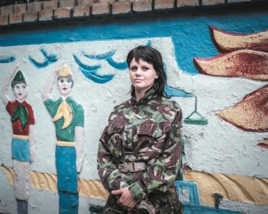 Masha, a hairdresser from Luhansk who joined the pro-Ukrainian Donbas Battalion last spring, at a training camp near Dnipropetrovsk, held in an old summer camp still decorated with Soviet-era Young Pioneers, July 2014; photograph by Justyna Mielnikiewicz from her series 'A Ukraine Runs Through It,' which has just been awarded the Aftermath Project's 2015 grant for photographic work documenting the aftermath of conflict. It will appear in