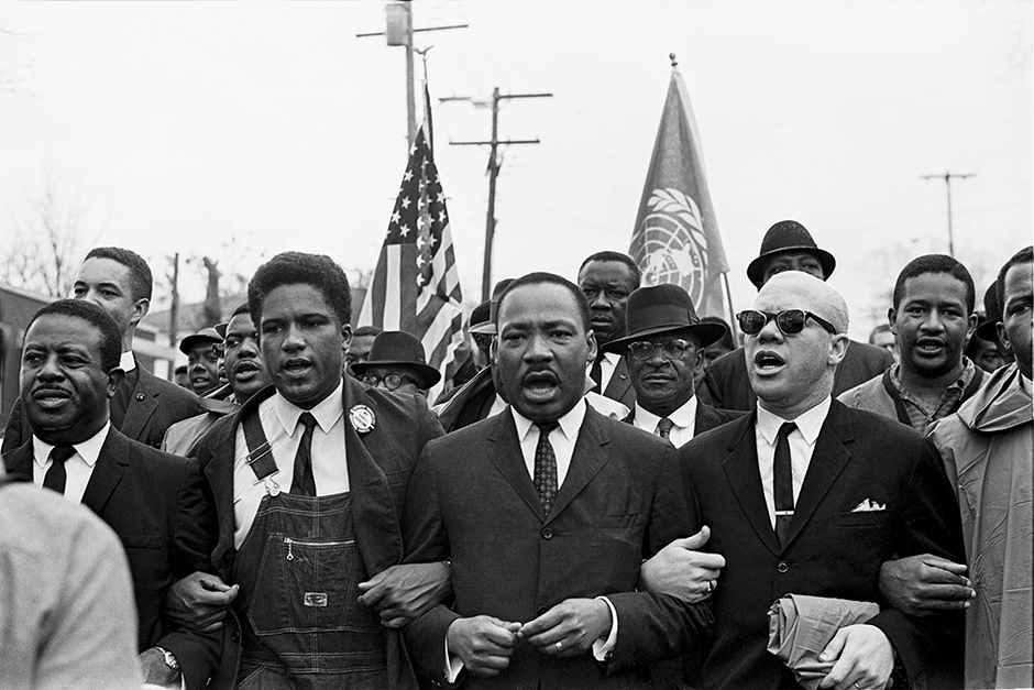 Martin Luther King Jr. with Ralph Abernathy, James Forman of the SNCC, and Reverend Jesse Douglas leading the march around the state capitol, Montgomery, Alabama, March 25, 1965; photograph by Spider Martin from the exhibition 'Selma March 1965,' at the Steven Kasher Gallery, New York City, March 5–April 18, 2015