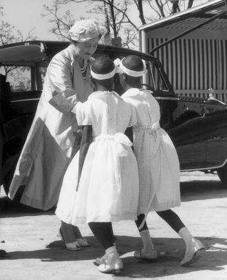 Queen Elizabeth the Queen Mother receiving flowers from local twin girls during a visit to Northern Rhodesia's copper belt, 1957