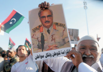 A supporter of the anti-Islamist campaign Operation Dignity holding a picture of its leader, General Khalifa Haftar, at a demonstration in Benghazi, Libya, May 2014