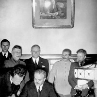 Soviet Foreign Minister Vyacheslav Molotov signing the Nazi–Soviet Pact, with German Foreign Minister Joachim von Ribbentrop directly behind him, next to Stalin, August 23, 1939