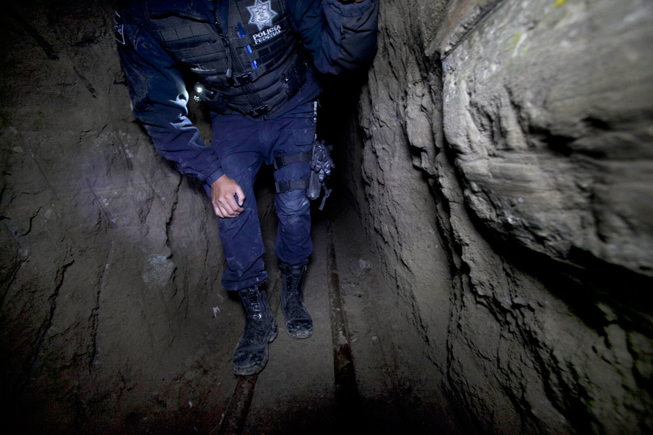 A Mexican federal police officer inspecting Chapo Guzmán's escape tunnel, July 16, 2016