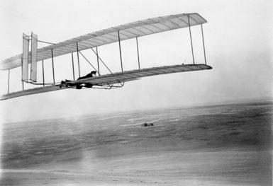Wilbur Wright flying his and Orville Wright's 1902 glider at Kitty Hawk, North Carolina, with the brothers' camp and shed visible in the distance, 1903