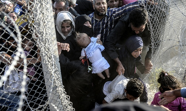 Syrian refugees rushing through a hole in the fence near the Turkish border, June 14, 2015
