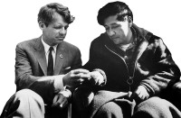 Robert Kennedy passing a piece of bread to Cesar Chavez at the end of Chavez's fast during the farm workers' strike against grape growers, Delano, California, March 1968