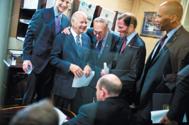 Senators Ron Wyden, Ben Cardin, Charles Schumer, Richard Blumenthal, Cory Booker, and Chris Coons (seated) before a news conference on Capitol Hill to introduce the Iran Policy Oversight Act, October 1, 2015