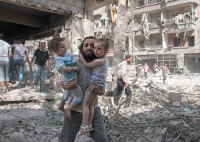 A Syrian man carrying his daughters across rubble after a barrel bomb attack on the rebel-held neighborhood of Kalasa in Aleppo, September 2015