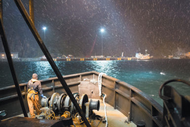 A crewman next to a winch on a crab boat entering the port of Dutch Harbor, Alaska, during an episode of The Deadliest Catch, October 2012