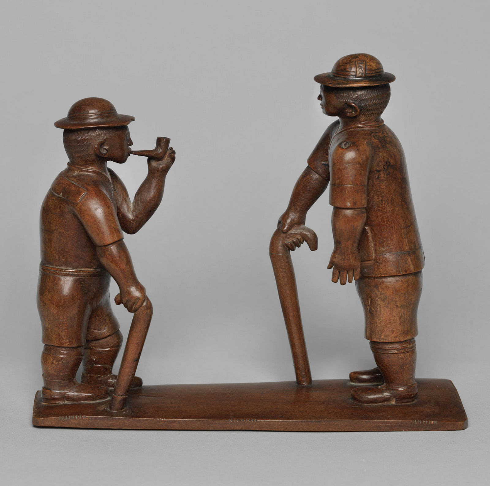 Kamba artist: Two European figures standing on a base, one with a stick and the other holding a pipe, circa 1900