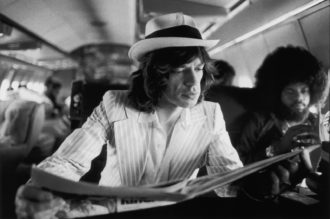 Mick Jagger and keyboardist Billy Preston on board the Rolling Stones' private jet during their Tour of the Americas, 1975