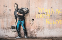 Apple founder Steve Jobs as 'the son of a migrant from Syria'; mural by Banksy,at the 'Jungle' migrant camp in Calais, France, December 2015