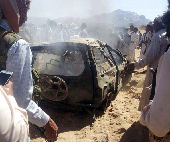 Yemenis gather around a burnt car after it was targeted by a drone strike, killing three suspected al-Qaeda militants, January 26, 2015