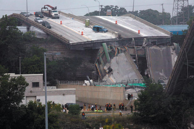 Rescue workers gathered below the Interstate 35W bridge in downtown Minneapolis after it collapsed and fell into the Mississippi River and onto its banks during evening rush hour, August 2007